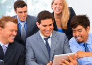 Business people happily use digital tablet during meeting.