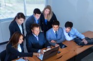 Business people use laptop, digital tablet during meeting.
