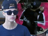 Bieber the bomber strikes again: Justin takes his bad graffiti skills Down Under by spray painting a wall in Australia... but did he break the law?