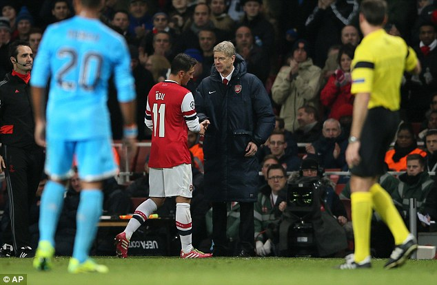 Key man: Arsenal boss Arsene Wenger greets Ozil after substituting him late on against Marseille