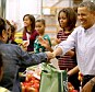 Helping hand: Barack Obama fist bumps with a woman as he and his family pitch in to pack bags of food for the poor, children and pensioners at a food bank in Washington