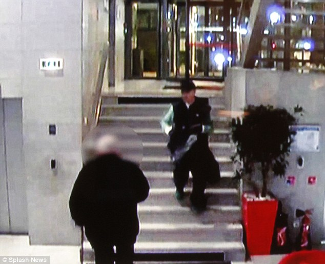 Intent: CCTV from inside the television station captures the moment the gunman, dressed in a black sleeveless top and carrying a large dark sack, calmly walks down the stairs towards the reception
