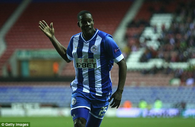 All smiles: Barnett celebrates his early goal with the Wigan supporters