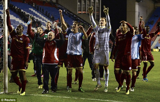 Still in it: Zulte Waregem players celebrate at the end of the match with their travelling fans