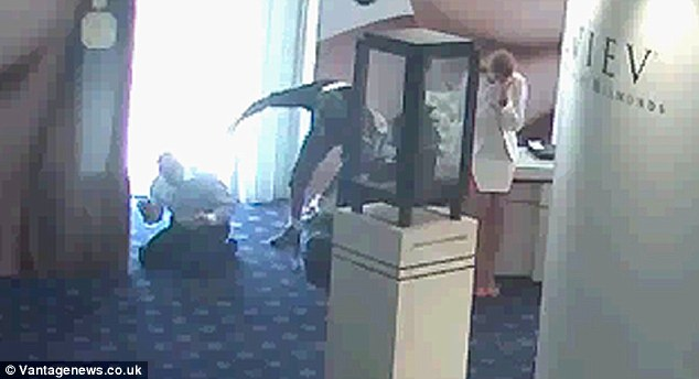 Loot: The man, still pointing his gun at a member of staff, reaches down and grabs a bag and display tray full of jewels