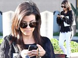 She's got her studs in order! Kourtney Kardashian takes care of business on her phone as she steps out in studded denim trousers and shaggy shirt