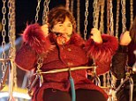 Here we go: Susan Boyle gamely takes a ride on the swings during her night out at Winter Wonderland on Thursday evening