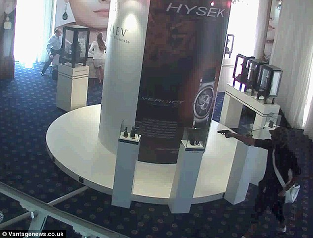 Brazen: The thief, bottom right of the picture, threatens staff with a handgun as he makes off with £88million of jewels from the Carlton Hotel in Cannes