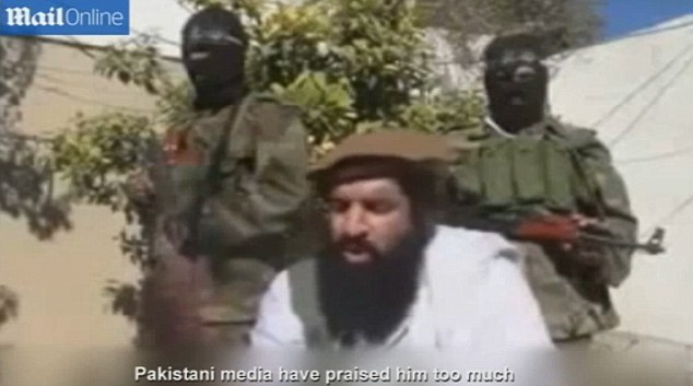 Hitting out: Flanked by two armed men a Taliban spokesman criticises Pakistani media coverage of Sachin Tendulkar's retirement