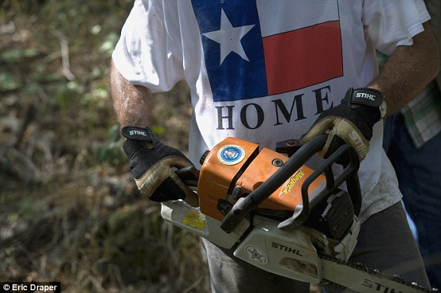 Cowboy president: The presidential seal adorns Mr Bush's chainsaw as he clears brush at the family ranch in Crawford, Texas