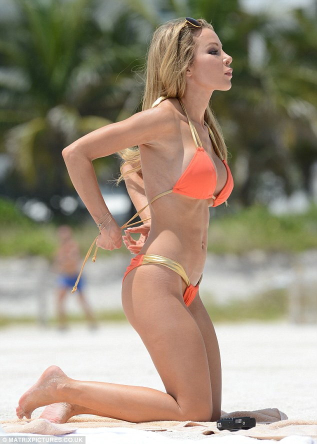 Still got it! The former Playboy model donned an orange and gold bikini which showed of her toned and taunt stomach