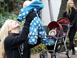 Caprice takes adorable baby sons Jett and Jax for stroll in the park wearing black leggings and polo-neck jumper