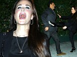 Screaming good time! Kyle Richards gets into a playful tussle with husband Mauricio while out to dinner