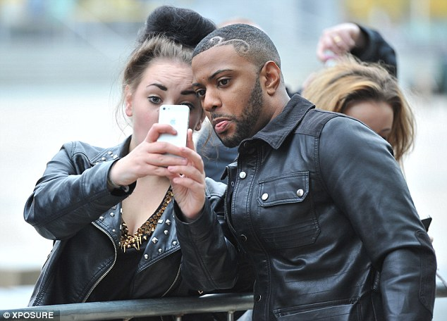 Poking fun: Oritshe sticks his tongue out as a female fan leans in with her iPhone
