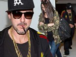 Couldn't wait? A Rastafarian-inspired David Arquette sparks up a cigar before he has even made it out of the airport with pregnant girlfriend Christina McLarty