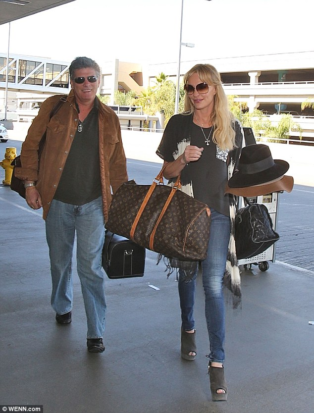 Mad hatter: Taylor Armstrong held a handful of hats as she and her fiance John Bluher arrived at LAX on Thursday