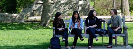 Four female students sitting on a bench in front of St. Michael's College.