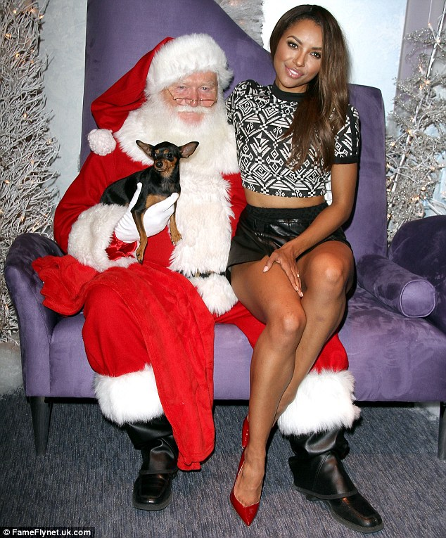 Ending on a happy note: The actress showed some skin in a crop top and shorts as she posed with Santa who held onto her dog