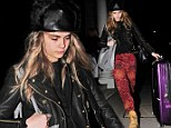 Hardworking girl: Cara misses the British Fashion Awards to head off to work accompanied by a shiny purple suitcase