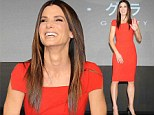 Miss Congeniality! Sandra Bullock flashes a smile as she stuns in a figure hugging red dress