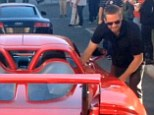 Final picture: Paul Walker stands next to the Porsche Carrera GY that he was killed in when it crashed and burst into flames in LA on Saturday