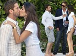 She's a feisty one! Mystery brunette lays a big one on Gerard Butler as they canoodle poolside in Miami... and he certainly doesn't object