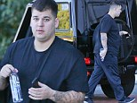 'It's hard and it takes time': Rob Kardashian reveals his fuller frame as he steps out in not-so-slimming black while sister Khloe lashes out at those calling her brother fat