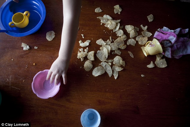 Chips are knocked across the floor as Michaelynn plays with a tea set