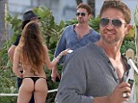Pretty as a picture! Gerard Butler eyes up brunette on the beach after posing up for photograph