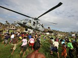 Filipinos rush to get relief goods during a helicopter aid drop