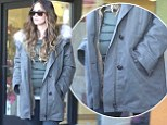 Pregnant Megan Fox's small baby bump pokes out of her hooded winter coat while buying beauty products