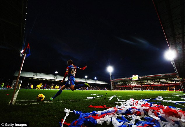 Darkness falls: Barry Bannan of Crystal Palace takes a corner under the floodlights at Selhurst Park