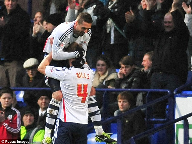 Celebrate good times: Andre Moritz (left) jumps on teammate Matt Mills after scoring Bolton's second goal