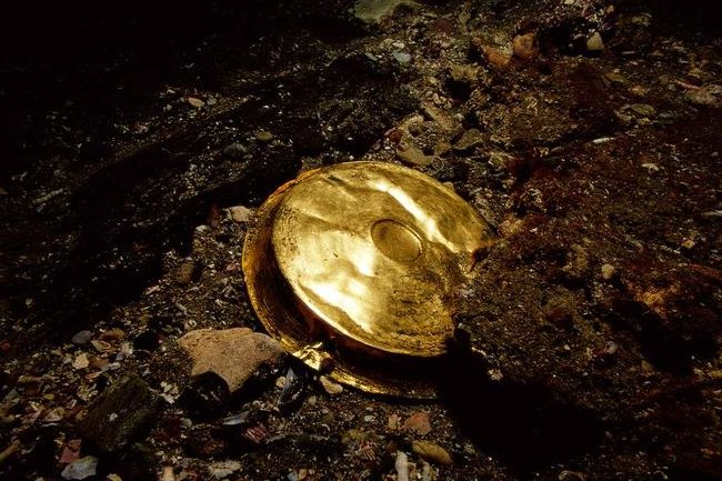 A gold vessel, which is a shallow dish used throughout the Hellenistic world for drinking.