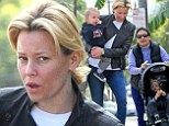 Fresh faced and fresh air: Makeup-free Elizabeth Banks gives a lift to her lookalike son Magnus as young Felix grabs a ride