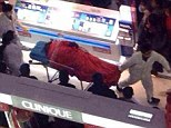 Tao Hsiao is carried out of the shopping mall on a stretcher but he was pronounced dead