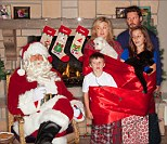 Odd holiday photo: Kelly Clarkson posted a bizarre Christmas card photo on Twitter with her family wrapped in decorations while gazing sideways at Santa