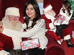 Giving Santa a heart attack! Victoria Justice perches on the merry man's lap at Delta Christmas event