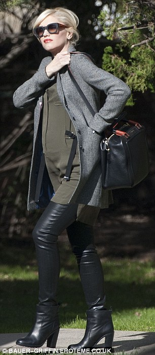 Stylish: The stunning mother wore leather skinny pants and a classy grey trench on the family day
