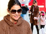 Keeping furry warm! Suri Cruise wears pink fluffy ear muffs as she heads into the blistering cold with her makeup and fuss-free mother Katie Holmes