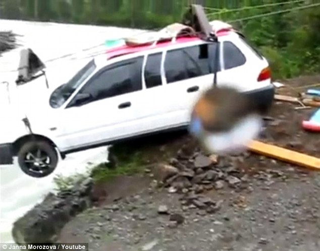 Ready for lift-off: The white estate car is gently lowered over the edge of a raging river on a zip-wire after a group of Russians found there was no bridge to cross