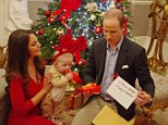 Dressed in a reindeer outfit, Prince George chews on a new pair of trainers, a Christmas present for the future King, as doting parents the Duke and Duchess of Cambridge look on