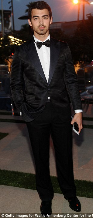 Suited and booted: Joe Jonas looked relaxed despite rumours dogging himself and the band after their cancelled their tour