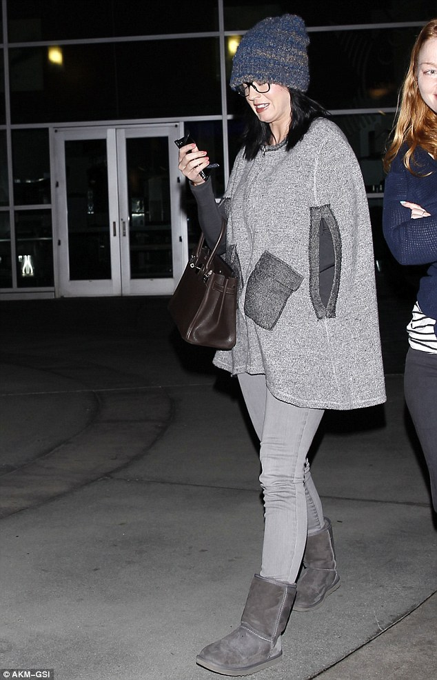 The caped crusader: Katy Perry wears a thick grey cape as she steps out in West Hollywood with a flame haired pal on Wednesday evening