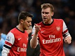 Pointing the finger: Per Mertesacker (right) explodes at Mesut Ozil following Arsenal's 6-3 defeat against Manchester City