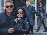 Alec Baldwin looks cheerful as he snuggles up to Hilaria on romantic stroll... after appearing annoyed while out in the snow