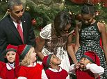 Say cheese! The president and first lady couldn't help but laugh as these children dressed as elves were up to no good during a photo op at the annual Christmas in Washington benefit concert