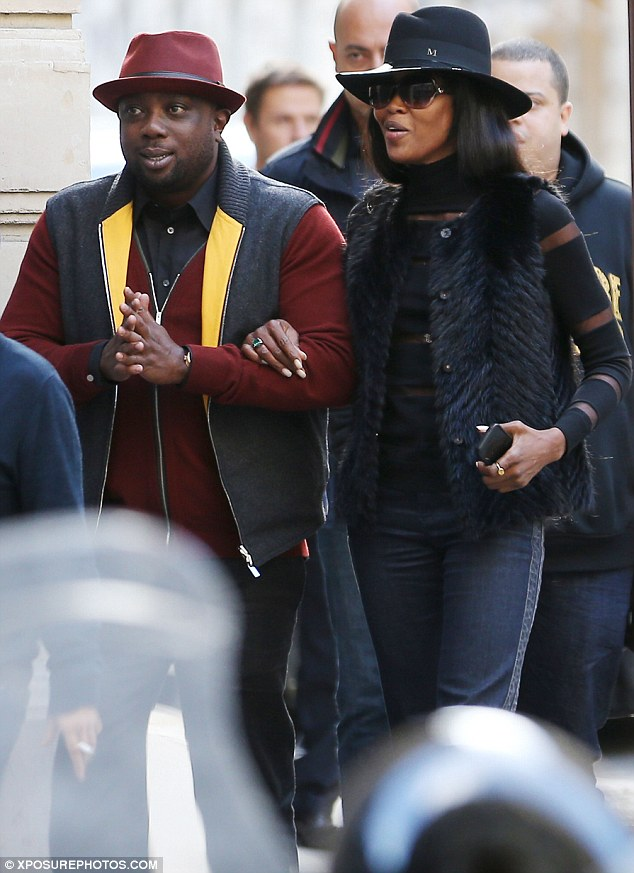 Linking arms: Naomi links arms with her friend as she shops on the Avenue Montaigne in Paris