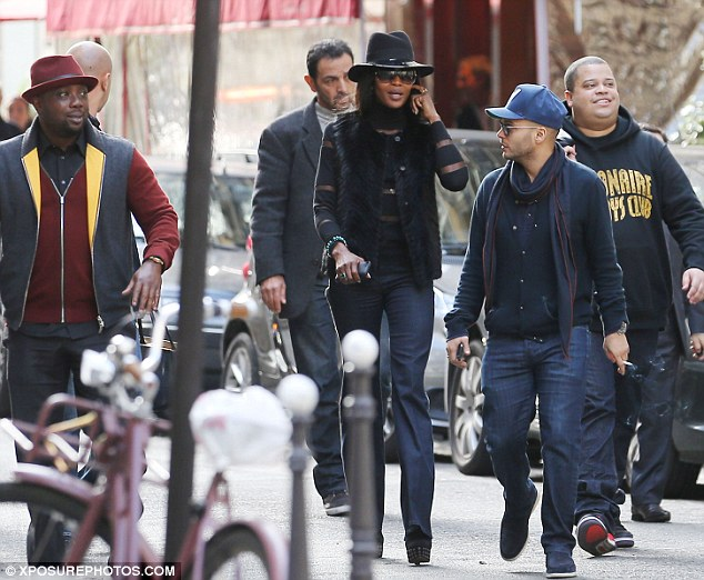 Out and about: The supermodel walked through the street with a group of male friends and towered above them all