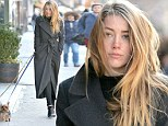 Dog lover: Amber Heard wore a black trenchcoat as she walked her dogs during a solo stroll on Monday in New York City